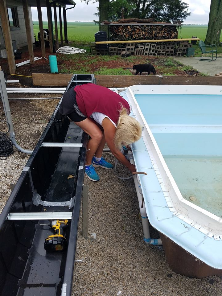 This image shows our semi-inground fiberglass pool shell. Kristie is setting our hanging braces that will support our plumbing lines as they wrap around the swimming pool. Once our concrete deck is poured all of this material will be covered up. The only component you will see is the deck and the swimming pool (right side).