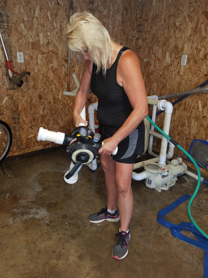 Here you can see Kristie, replacing the manifold system for this sand filter. The PVC riser & replacement laterals are shown on the back end of this manifold system. The black valve with the handle is the diverter assembly that controls the flow of water going in and out of the filter system.
