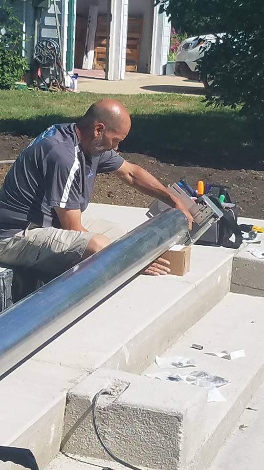 Here we're finishing up the final touches of our cover installation. Our safety cover will wrap around this steel cylinder. This keeps the material smoothed out and wrapped tightly when not in use.