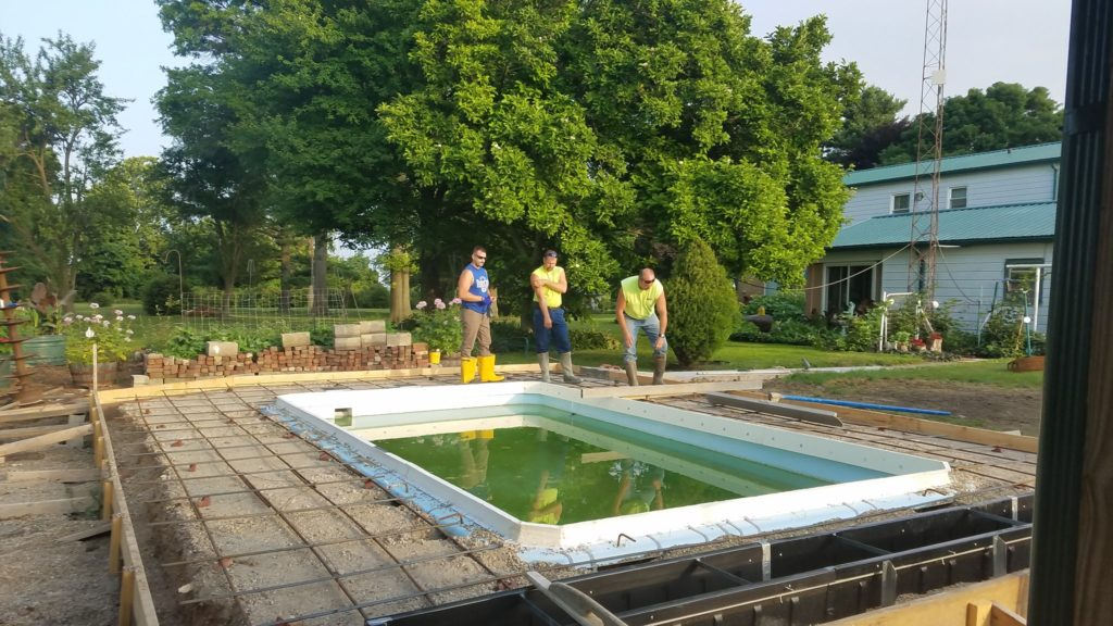 "Prior to pouring our concrete deck, we had to complete the ""prep work."" This involves ""forming"" our fiberglass pool with the white styrofoam Stegmeier forms (shown above). We also had to set framework (wood border) and lay our network of rebar in a 12""x12"" grid."