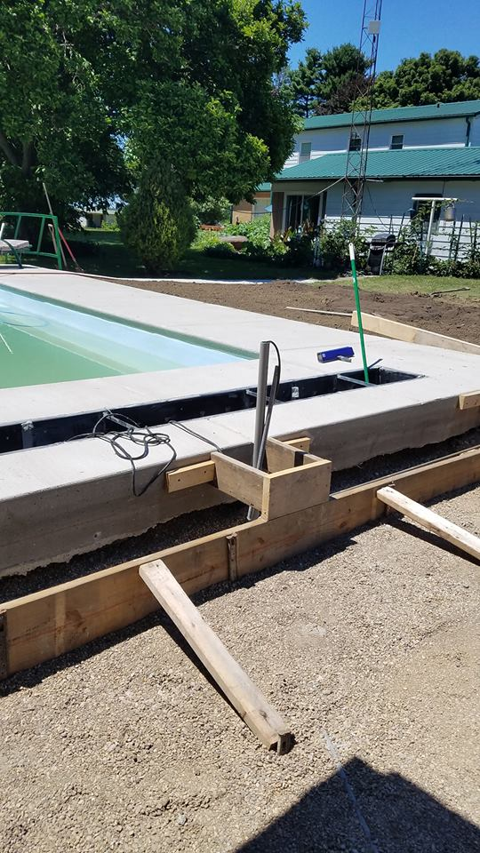 "This image shows our Polybox (black rectangular box) which will house our Automated Swimming Pool Cover. Polyboxes are perfect compartments for this type of swimming pool accessory. It's also a necessary component that allows us to store and essentially ""hide"" your automated pool cover when it is not in use."